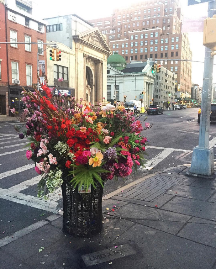 "The artist, Lewis Miller, is a floral designer for weddings and parties, but started putting his ""Flower Flashes"" — many of them in trash can ""vases"" — around the city a few months ago.""Gifting flowers to New Yorkers is a simple idea that I have been thinking about for years,"" Lewis told Vogue. ""I am in the business of fantasy and flowers, and it's my job to transform key moments in my clients' lives into joyful, everlasting memories. I wanted to recreate a similar feeling for the everyday city-dwellers and tourists of New York City."""