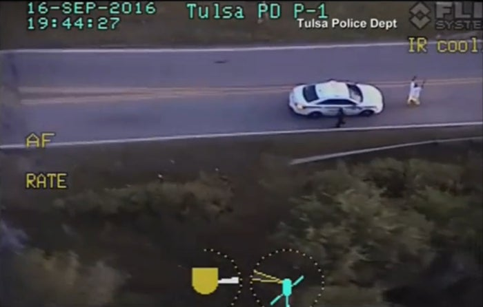 A still image captured from a helicopter video shows Terence Crutcher with his hands in the air, followed by a police officer with a drawn weapon.