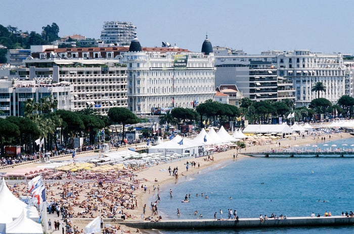 Tourists lounge on the beach during Cannes in May 1998.