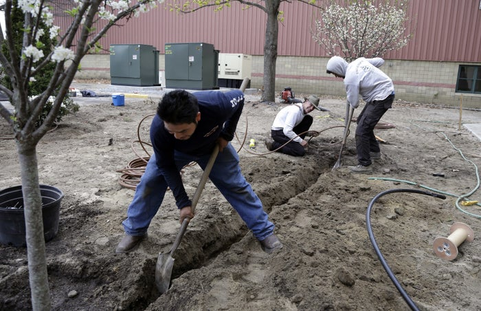 Stephen Faulkner, middle, owner of Faulkner's Landscaping & Nursery, installs an irrigation system alongside his workers Gonsalo Garcia, left, and Jalen Murchison, right, at a landscape project in Manchester, N.H.