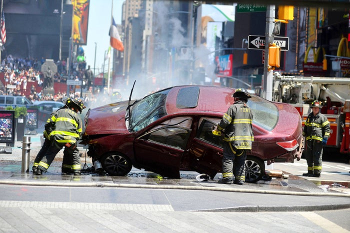 Firefighters surround the car that driver Richard Rojas used to ram into pedestrians in Times Square, killing one woman and injuring more than 20 other people, on May 18. Rojas was arrested at the scene and later charged with murder, attempted murder, and aggravated vehicular homicide.