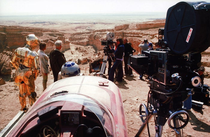 Anthony Daniels as C-3PO, Mark Hamill as Luke Skywalker, Alec Guinness as Obi-Wan Kenobi, and Kenny Baker as R2-D2 are directed and filmed in Tunisia on the set of Star Wars: Episode IV in 1976.