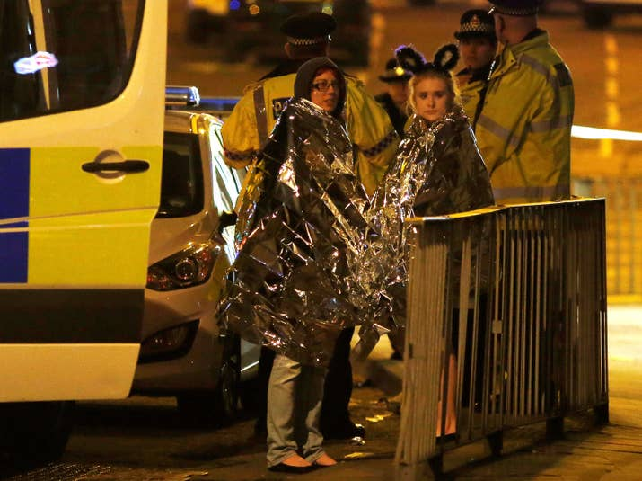 Two women wrapped in blankets stand near the Manchester Arena Monday night.