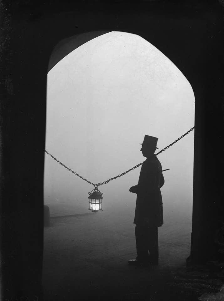Un hombre pasa cerca de una lámpara un día de niebla en Londres (1934).