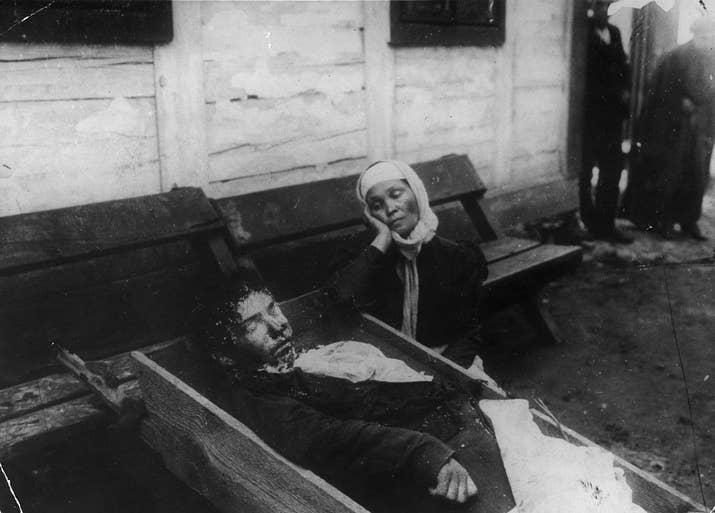 Una mujer, junto al cadáver de un familiar que murió asesinado en un linchamiento (aproximadamente 1900).