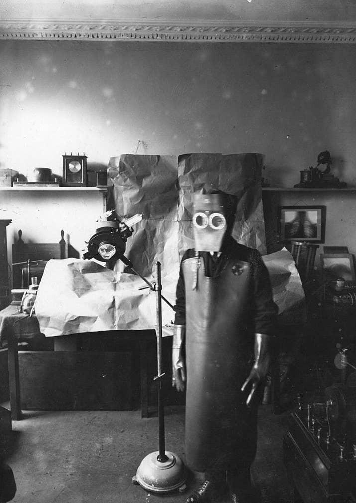 Un operario vestido con prendas protectoras se prepara para hacer unos rayos X (1909).