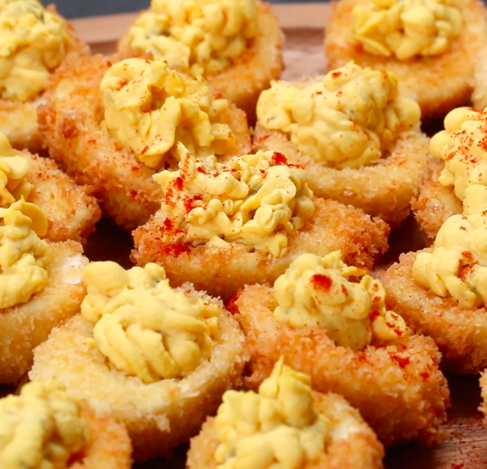 Makes: 24 deviled eggs INGRIDIENTS 12 peeled hard-boiled eggs1 cup flour3 eggs, whisked1 cup panko bread crumbsOil for frying4 tablespoons mayonnaise2 tablespoons pickle relish2 tablespoons mustard1 teaspoon hot sauceSalt, to tastePepper, to tastePaprika, to taste PREPARATION 1. Cut the hard-boiled eggs in half lengthwise. Gently separate the cooked egg white from the yolk and transfer to a medium bowl.2. Coat the cooked egg whites in flour, eggs, and panko bread crumbs. 3. Heat cooking oil for deep-frying in a medium-size pot over medium heat. Carefully place eggs into the hot oil. 4. Fry for 2-3 minutes, flipping halfway through. Remove from pot and drain excess oil on a paper towel.5. Add mayonnaise, relish, mustard, hot sauce, salt, and pepper to the yolks and mash until smooth.6. Fill a piping bag or plastic sandwich bag with yolk mixture. Pipe mixture back into the fried egg white, dust with paprika, and serve!