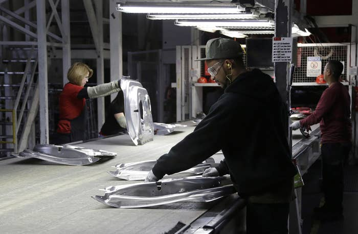 Tesla employees work in the Tesla factory in Fremont, Calif., Thursday, May 14, 2015. (AP Photo/Jeff Chiu)