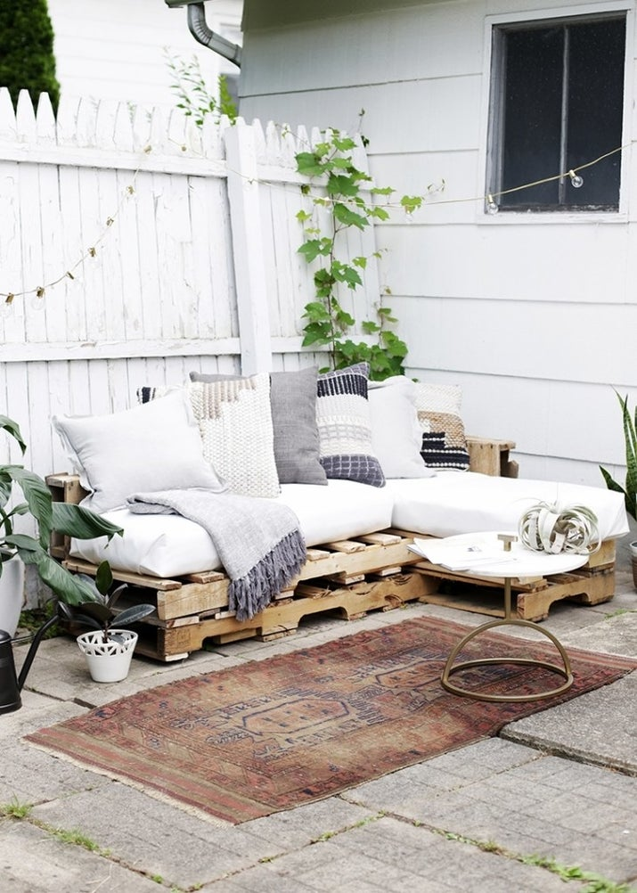Outdoor furniture is hella expensive whereas all you need to purchase for this pallet couch from The Merry Thought is the cushions.