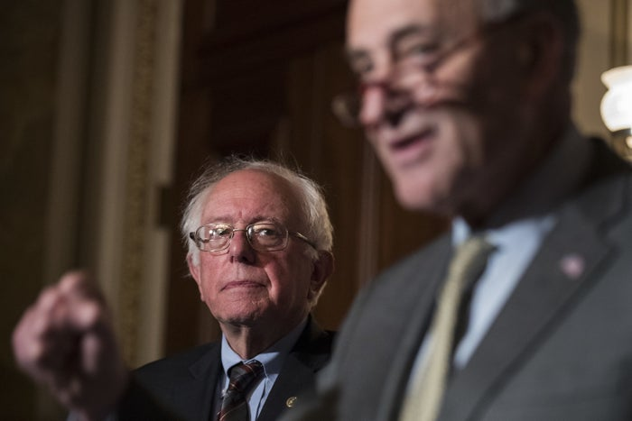 Sen. Bernie Sanders looks on as Senate Minority Leader Chuck Schumer calls to raise the minimum wage to $15 an hour.