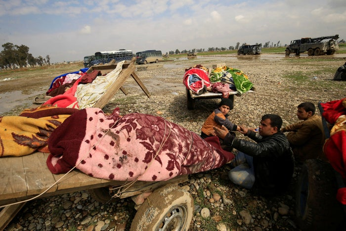 Carts loaded with bodies of civilians killed in an air strike in Mosul