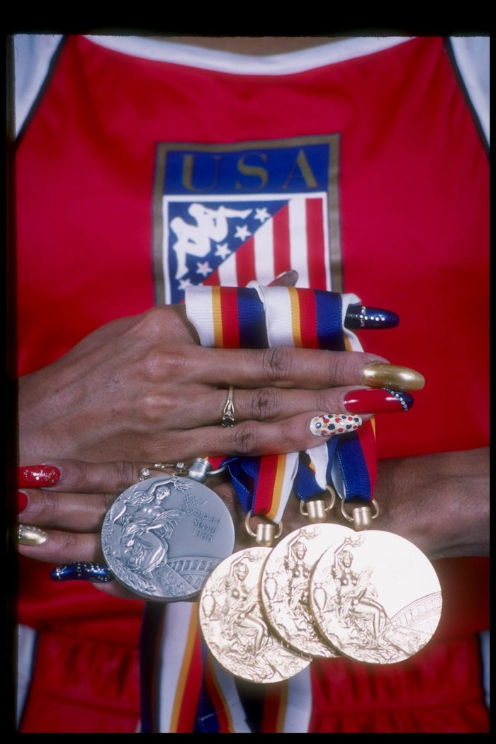Florence Griffith-Joyner holds her medals won at the 1998 Olympics in Seoul, South Korea.