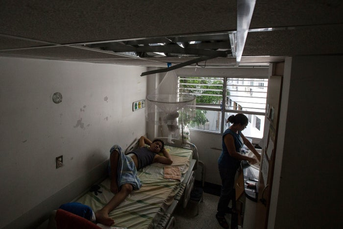Maikol and his mother Taina Mendoza in their room, which has no lights or air conditioning, at the hospital JM de los Ríos, Caracas.
