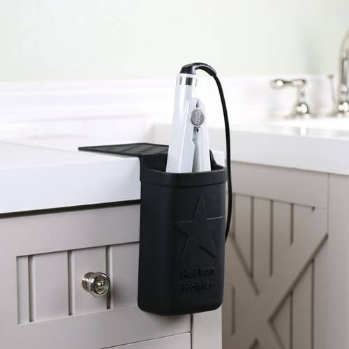"""Promising review: """"This holster is a great space saver and prevents me from knocking it off my counter, which I always do in result of breaking my flat iron numerous times! I was surprised by how big it was. It fits my standard flat iron perfectly with some space to spare, I could fit a brush in there. I love that it holds up to 500 degrees, which my flat iron goes up to 450 degrees so I am able to keep my flat in there while it is in use."""" —ashleywhyGet it from Amazon for $17 (available in pink, purple and white)."""