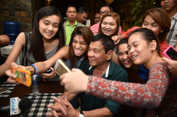 Philippines' President Rodrigo Duterte, poses for selfie pictures with supporters, after speaking to the media for the first time since he claimed victory in the presidential election, at a restaurant in Davao City, on the southern island of Mindanao on May 15, 2016.
