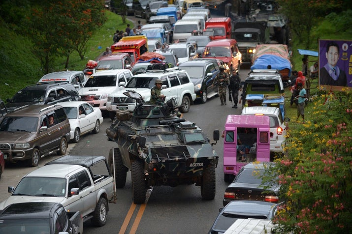 An armored personnel carrier moves amongst stuck vehicles of residents fleeing Marawi, in the southern island of Mindanao on May 25, 2017, as fighting rages between government forces and gunmen who have pledged allegiance to the Islamic State group.