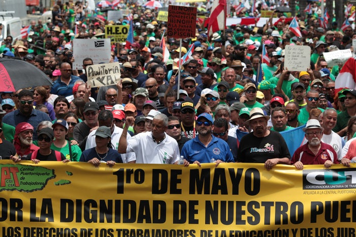 "People march during a protest against the government's austerity measures as Puerto Rico faces a deadline on Monday to restructure its $70 billion debt load or open itself up to lawsuits from creditors, in San Juan, Puerto Rico May 1, 2017. The sign reads: ""May 1st, for the dignity of our people."""
