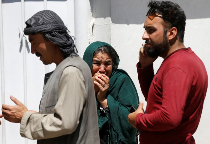 Relatives of Afghan victims mourn outside a hospital after a blast in Kabul.