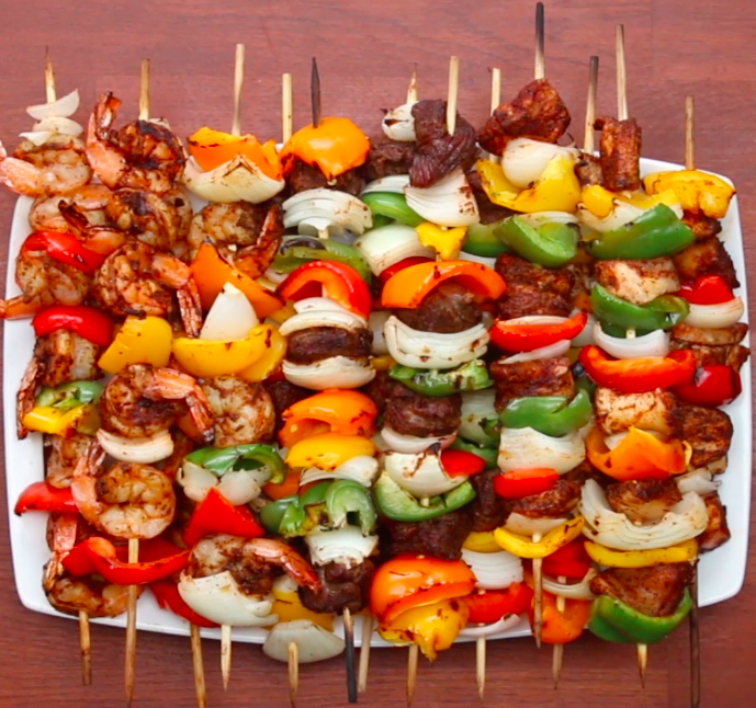 Servings: 12-14INGREDIENTS1-2 onions, quartered6 bell peppers, cut in 1.5-inch squares1 pound cubed steak1 pound cubed chicken breast1 pound shrimp, deveined and peeled with the tail on3 teaspoons salt (1 teaspoon per protein) 3 teaspoons pepper (1 teaspoon per protein) 3 tablespoons garlic powder (1 tablespoon per protein)3 tablespoons chili powder (1 tablespoon per protein)3 teaspoons cumin (1 teaspoon per protein)PREPARATION1. Place each meat in a gallon-sized plastic bag and cover with spices ingredients. Close the bag and shake until evenly coated.2. Prepare skewers by layering onion, bell pepper, and protein. (Be sure not to mix proteins on the same skewer, as they have different cook times.)3. Grill the skewers over medium-high heat, flipping once, until the protein's internal temperatures are as follows: a) Steak - 155ºF/70ºCb) Chicken - 165ºF/75ºCc) Shrimp - 145ºF/65ºC4. Enjoy!