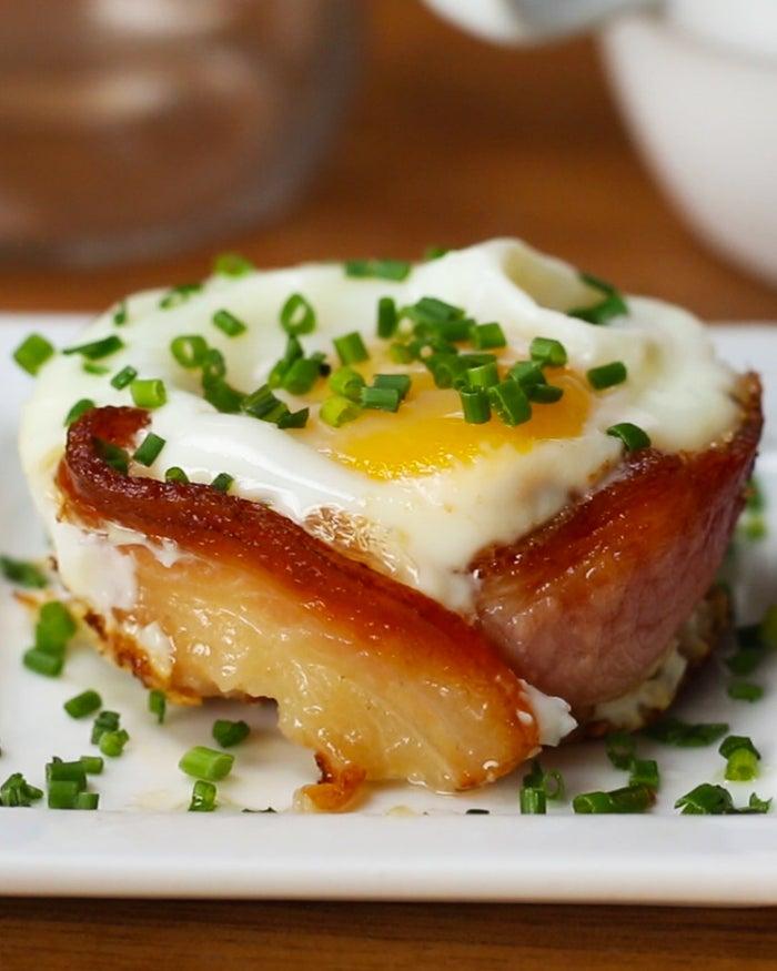Você vai precisar de:6 fatias de bacon6 ovos Sal a gostoPimenta a gosto¼ de xícara de queijo cheddar, ralado Cebolinha Equipamentos especiais:Bandeja de muffinModo de preparo:Preaqueça o forno a 200° C.Coloque as fatias de bacon em círculos na bandeja de muffin. Asse o bacon por 10 minutos. Coloque um ovo inteiro em cada uma das formas e coloque sal, pimenta e o queijo cheddar ralado. Leve ao forno novamente por 10 minutos, ou até que a gema esteja na consistência desejada. Passe uma faca em volta de cada muffin para soltar e removê-lo. Finalize com cebolinha e é só saborear!Porções: 4-6