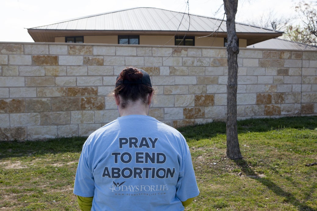 An anti-abortion activist prays outside a Planned Parenthood clinic on February 22, 2016 in Austin, Texas.