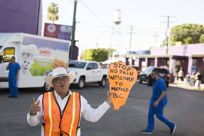 """Guillermo """"Memo"""" Perez Angulo stands at the US–Mexico border to encourage people to visit his employer's dental clinic May 18, 2017, in Los Algodones, Mexico."""