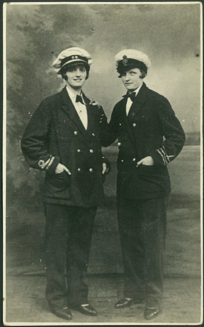 Two women in Navy uniforms pose for a studio portrait, circa 1920s.
