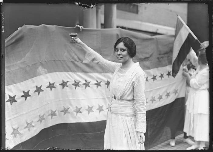 Alice Paul makes a toast to Tennessee's ratification of the 19th Amendment to the U.S. Constitution, giving women the right to vote. The banner beside her was displayed outside the National Women's Suffrage Party Washington, DC, headquarters showing the stars of the states which had ratified the amendment.