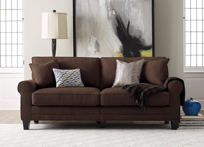 A Brown Sofa Covered In Velvet Textured Fabric