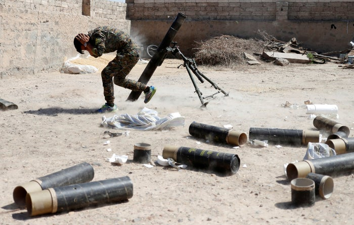 A YPG fighter fires a mortar round.