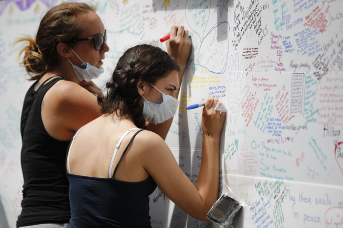 Well-wishers write messages on a wall of condolence following the blaze at Grenfell Tower on 14 June 2017.
