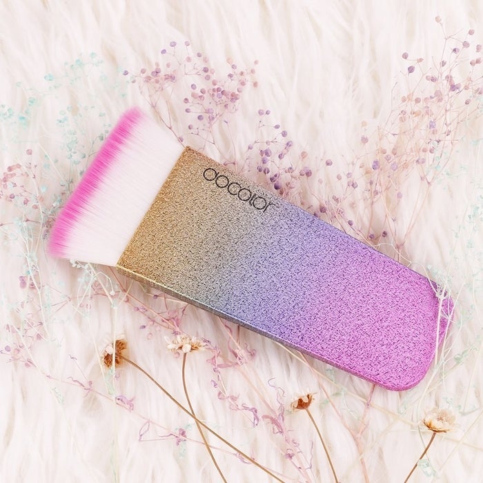 """Promising Review: """"This flat contour brush is AMAZING! The brush looks so pretty with the glitter and bright colors. The brush tip is pink and beautiful. The brush works great, too. You get very straight lines and a sharp contour. Bristles are very soft and it's so affordable!"""" —MargieGet it from Amazon for $9."""