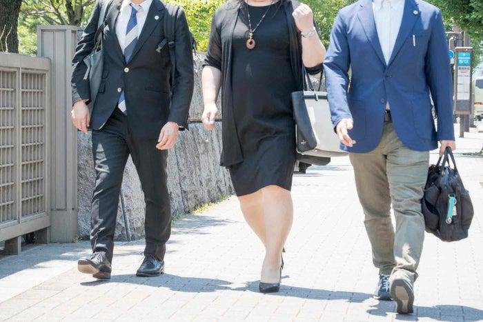 京都地裁に入る甲野さん(中央)と代理人弁護士たち