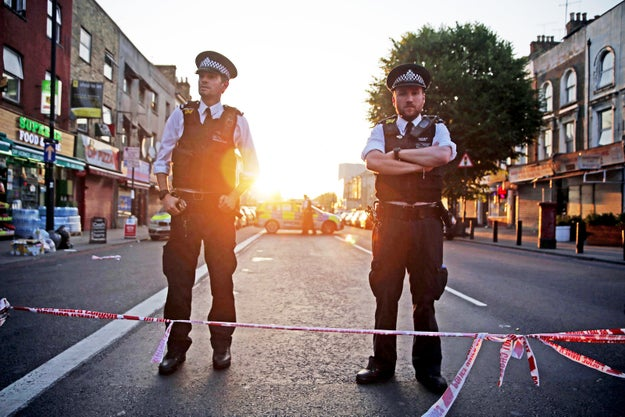Dawn breaks on the morning of 19 June as police guard a street near the scene of the attack.