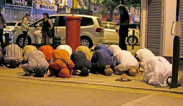Muslims pray on a sidewalk near the scene of the attack.