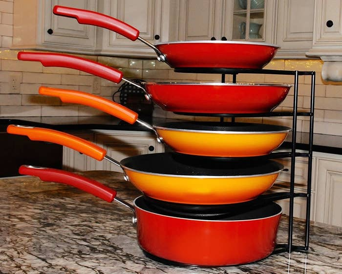 """Pots and pans: are they cooking necessities, or are they drums? You decide. Promising review: """"Before I bought this, I would have to stack my cast-iron pans on top of each other, which meant I had to lift one pan to get to another one. Now, they are neatly organized in my cabinet and I can very quickly go straight for the exact one I need—without having to pick up the whole collection. Very sturdy and tolerates the weight of the whole collection without giving. Love it!"""" —Dawn WhittGet it from Amazon for $19.95."""