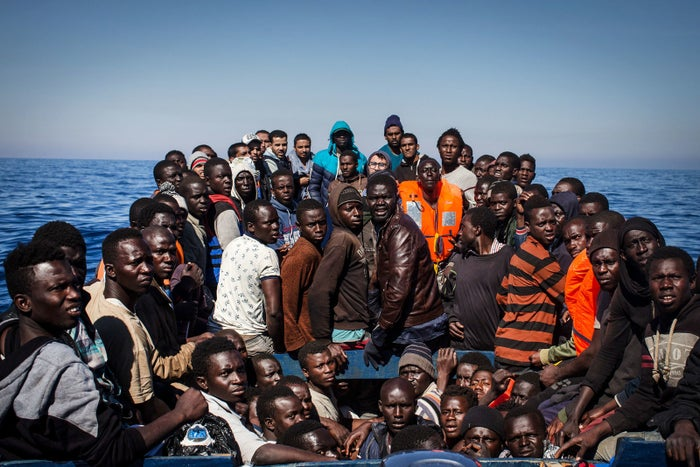 Refugees and migrants wait to be rescued from a small wooden boat on May 18, 2017, off the coast of Lampedusa, Italy.