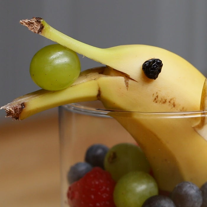 Here's what you'll need: 1/2 cup assorted fruit, 1 halved banana with fins and mouth cut, 1 green grape, 2 raisins, and 1/4 teaspoon peanut butter.