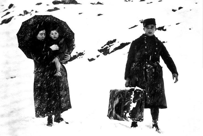 Un soldado francés lleva el equipaje de una refugiada española en un paso de montaña.