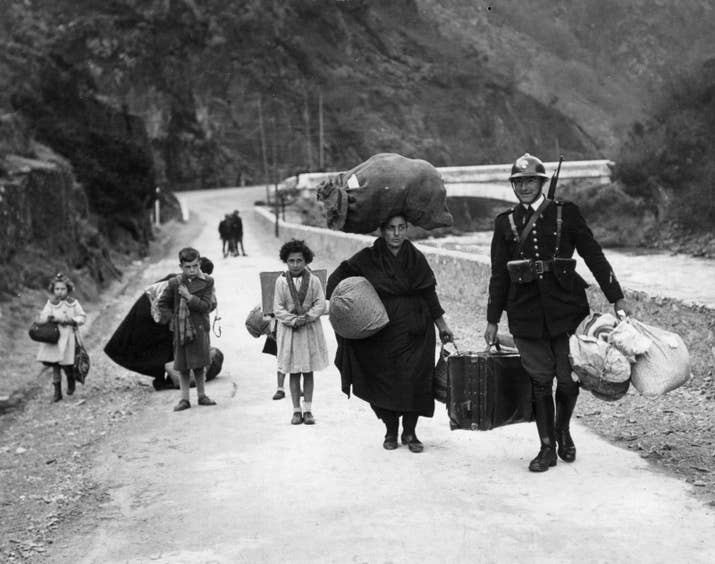 Un soldado francés ayuda a una familia de refugiados a cruzar la frontera en 1938.