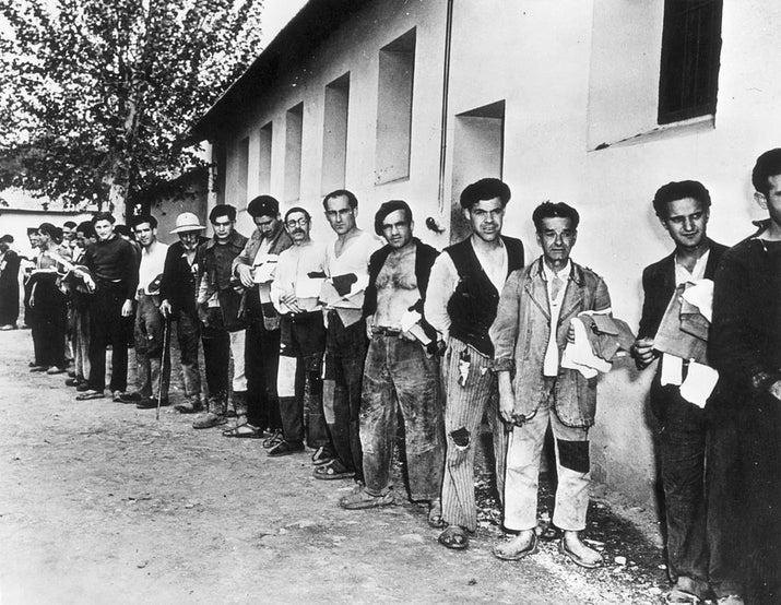 Refugiados españoles en el norte de África forman una fila para recibir zapatos nuevos (1939).