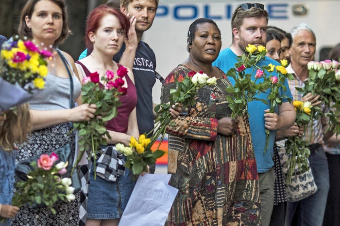 hold flowers as they attend a vigil outside Finsbury Park Mosque on 19 June.