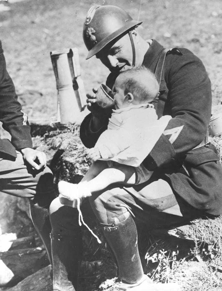 Un soldado francés de las tropas fronterizas alimenta a un bebé refugiado que acaba de cruzar la frontera el 3 de abril de 1938.