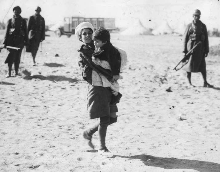 Una niña lleva a su hermano en la frontera con Francia. Llegó caminando desde Figueres y sería enviada a un campo de refugiados con otros compatriotas.