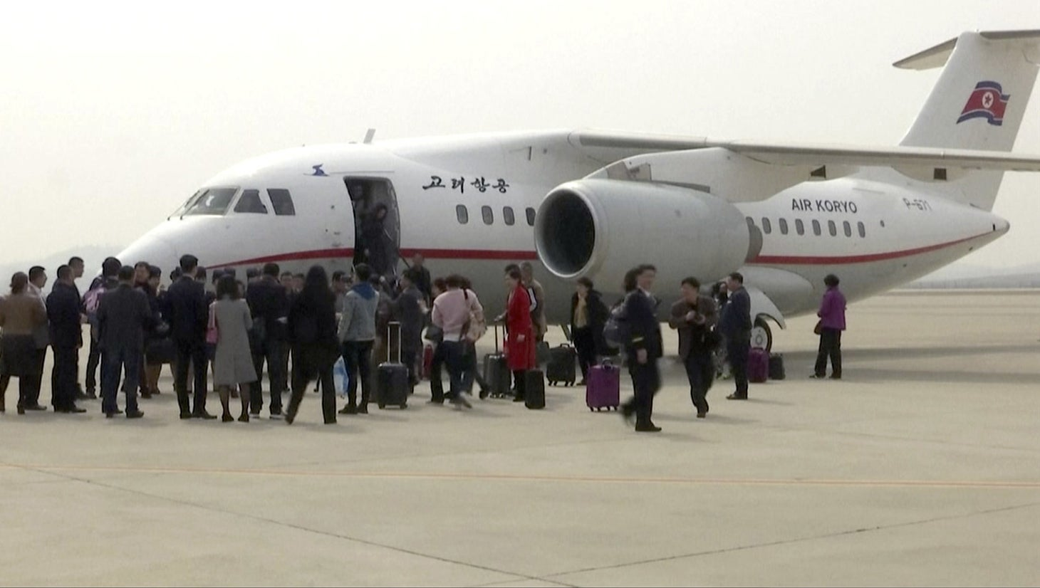Tourists leave an Air Koryo plane in Pyongyang.