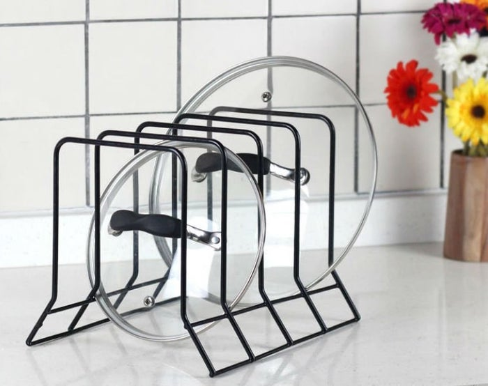 """Promising review: """"I ordered two of these racks to organize the hot mess that is my cabinets. They're sturdy and work well! My pans are organized and easy to access. It almost looks like an adult lives here!"""" —ButchGet it from Amazon for $8.87."""