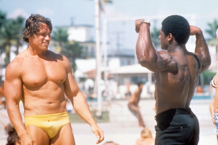 Arnold Schwarzenegger admires the muscles of another bodybuilder at Muscle Beach in Los Angeles, 1977.