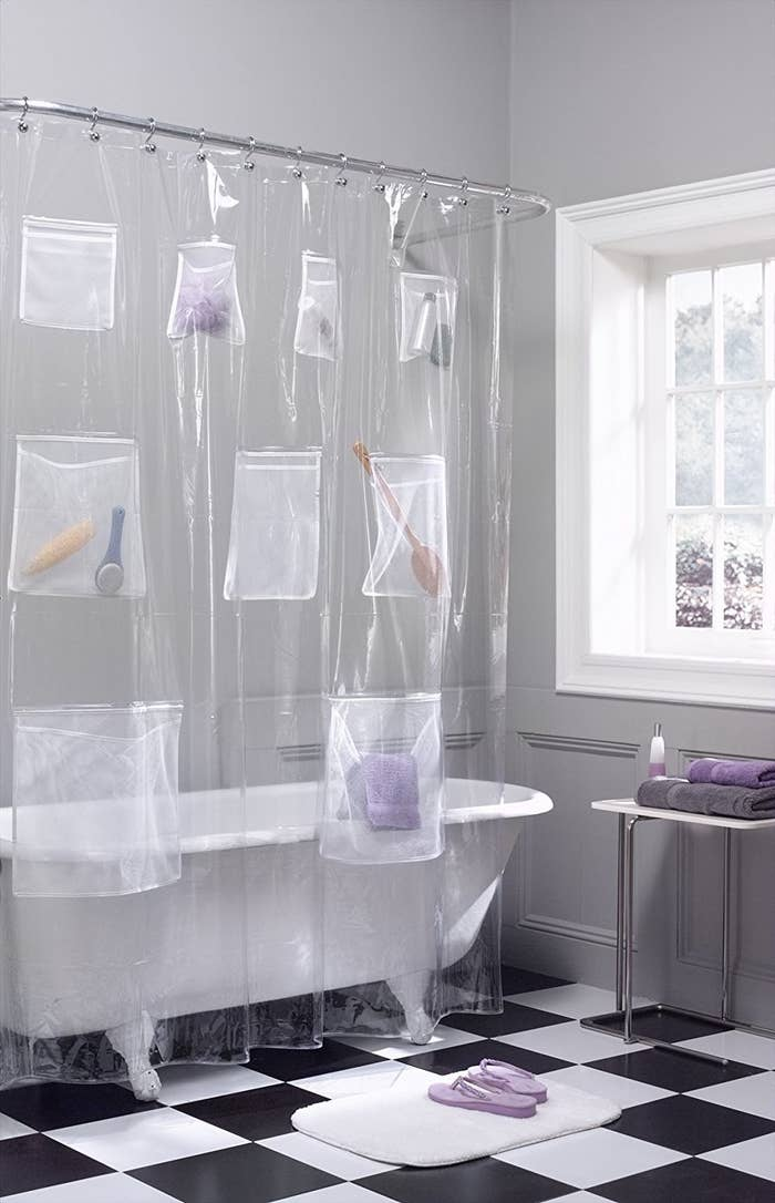 clear shower curtain with pockets holding bathroom accessories