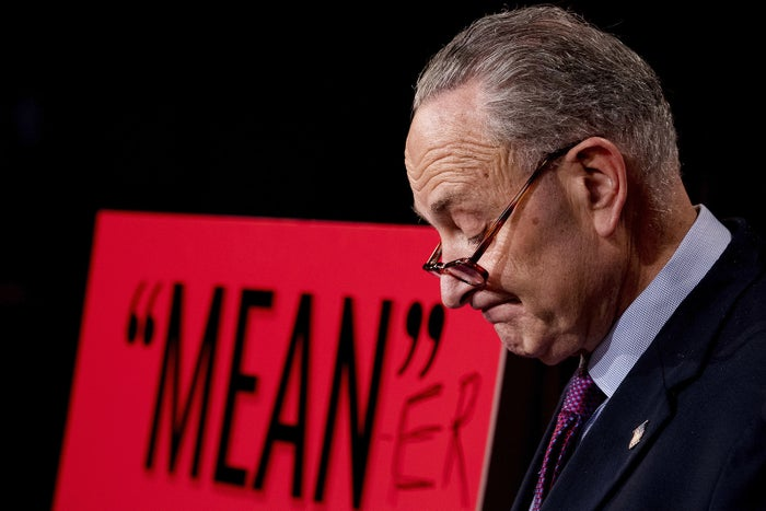 """Senate Minority Leader Chuck Schumer pauses after writing """"-er"""" on a sign with a purported by President Donald Trump, his response to the release of the Republicans' health care bill, which represents the long-awaited attempt to scuttle much of President Barack Obama's Affordable Care Act, at the Capitol in Washington, DC, on June 22."""
