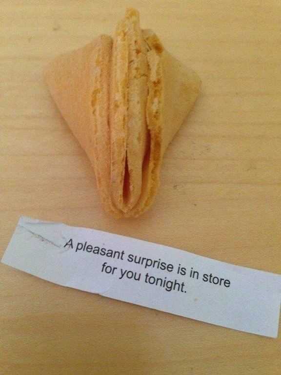 A fortune cookie broken in half and a message that says a pleasant surprise is in store for you tonight